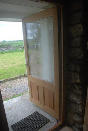 Porte d'entrée vitrée en chêne en position ouverte