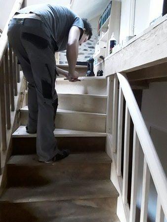 Menuisier travaillant à la modification de la sortie d'un escalier droit