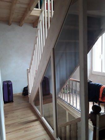 Vue de palier d'une cloison vitrée autour d'un escalier ancien rénové